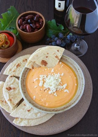 Greek Feta and Roasted Pepper Spread with Flat Bread on www.cookingwithruthie.com is an addictive reddish orange cheese spread that you won't be able to stop eating!