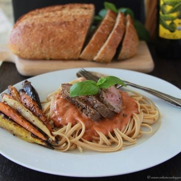 Steak & Linguini Pasta with Creamy Tomato Basil Sauce Recipe | Our Steak & Linguini Pasta with Creamy Tomato Basil Sauce Recipe is simple to make and the flavor combination is pure heaven! We start off with a beef loin strip steak, add steak rub and broil it on a sheet pan with multi-colored carrots. While it cooks we make noodles and a simple sauce so dinner is on the table in less than 30 minutes and making for a perfect weeknight meal! || cookingwithruthie.com