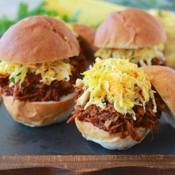 Pulled Pork Sliders with Pineapple Slaw is fabulous to make for big summer gatherings- it'll be a hit! www.cookingwithruthie.com