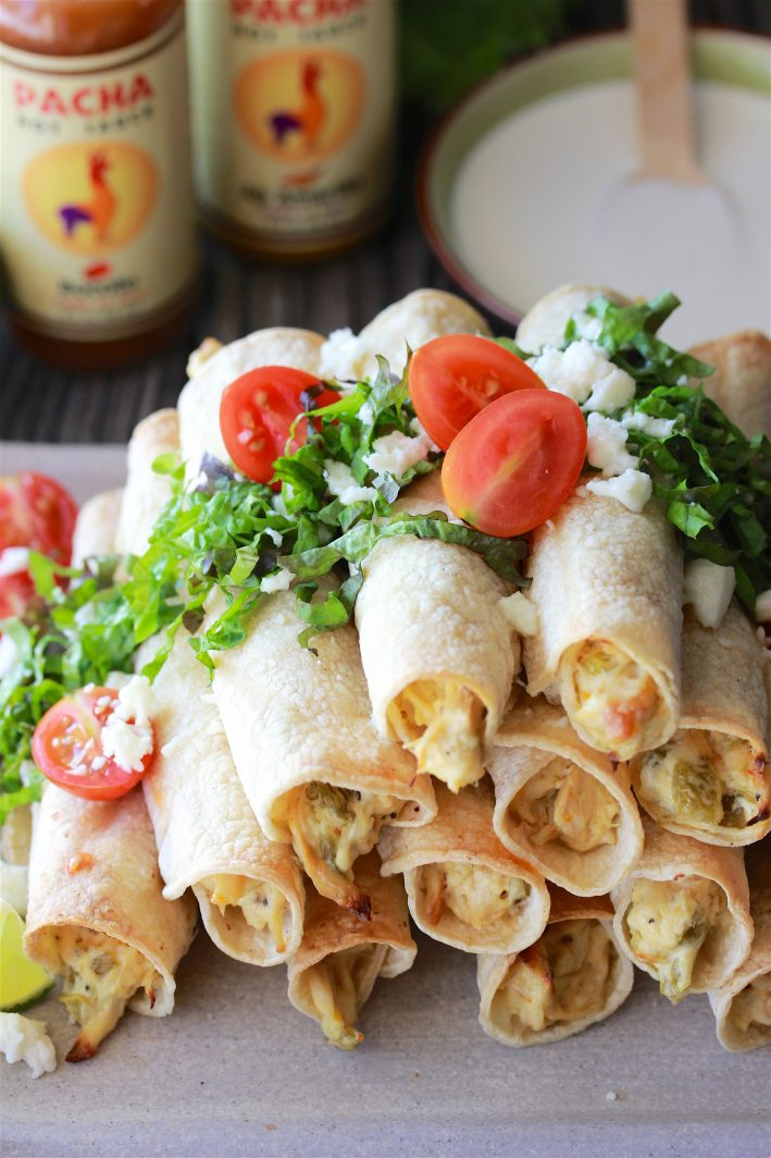 Our Green Chili Chicken Baked Flautas with Spicy Crema Recipe puts a healthier spin on this Mexican cuisine classic for your dinner table tonight! by cookingwithruthie.com